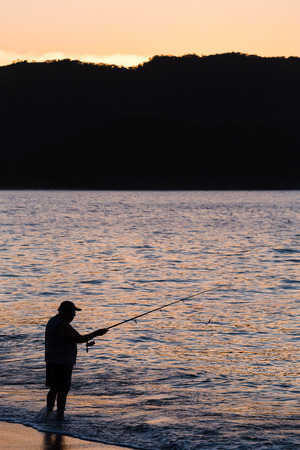 A tico fishes on a beach at Guancaste in Costa Rica at dusk. Banco de Imagens