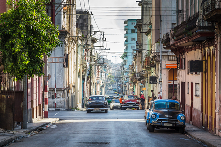 A number of old cars from the 1950s travel up hill between colourful & dilapidated buildings of Centro Havana.