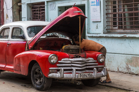 A man getting under the bonnet of his old timer in Centro Havana.  Since the US embargo, the Cuban people have literally done anything they can to keep their cars on the roads.
