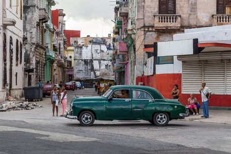 wheelie: A typically colourful street in Centro Havana featuring a pile of rubble, large wheelie bins, rugged buildings, locals waiting for buses & of course a vintage car.