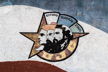 Close-up of a motif of the Young Communist League in Havana showing the faces of Julio Antonio Mella, Camilo Cienfuegos and Che Guevara.  The motto is Estudio, Trabajo, Fusil and means Study, Work, Rifle.