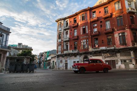 鮮やかな赤のビル前を通過するこの赤ヴィンテージ車を見たときは低太陽、キューバのハバナの通り長い影を落としてください。