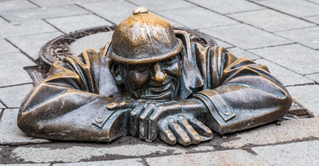 CumilRubberneck leaning uot of a man hole cover in Bratislava.