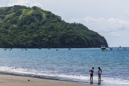 Local people talking on the Coco Beach as private boats occupy the background.
