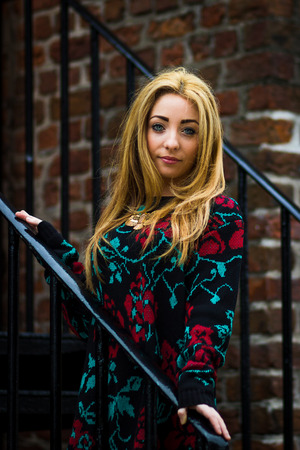 Alexs long hair flows either side of her face as she stands on some steps by the Albert Dock in Liverpool.