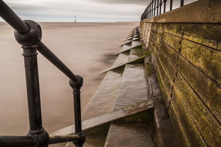 Water laps against the steps of the retaining wall on the Sefton coastline at high tide.  This was captured part way down some steps leading down to the beach from the promenade. Stock Photo