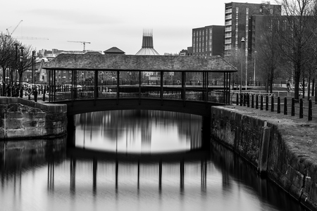 paddys day: The Metropolitan cathedral & a footbridge reflect on the water of Dukes Dock in Liverpool.