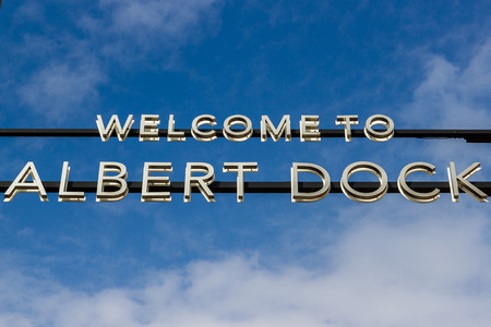 Signage under a gorgeous blue sky which meets visitors to the Albert Dock on the Liverpool waterfront.