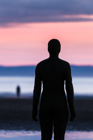 The warm sunset makes way for twilight on Crosby beach, home to 100 life sized cast iron statues.  Another model can be seen in the distance closer to the waters edge.