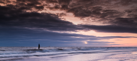 mersey: The colourful light reflects on the incoming tide at Crosby beach, silhouetting one of the Iron Men.  In total there are 100 cast iron statues modelled on & created by Anthony Gormley along this stretch of coast.