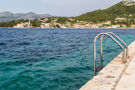 Steps lead down from the quayside on the Croatian island of Lopud and into the turquoise Adriatic Sea.