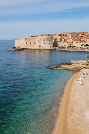 Waves lap up against the Banje Beach, a popular upmarket stretch of pebbled coast with stunning views of the old town of Dubrovnik.