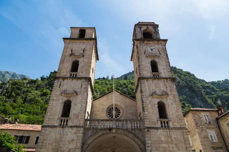 Kotor Cathedral pictured against the east side of Kotor -  backing into a cliff face with a meandering defensive upper town wall climbing the mountainside.  The building was damaged & had to be rebuilt following the 1667 Dubrovnik earthquake however they