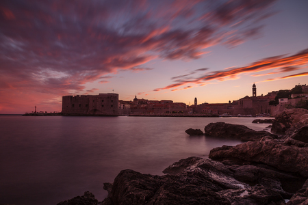 long johns: The early summer sunshine dips below the horizon as the sky turns pink over Dubrovnik and its old harbour.