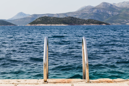 former yugoslavia: Steps lead down from the quayside on the Croatian island of Lopud and into the turquoise Adriatic Sea.