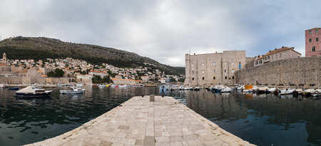 A multiple image panorama of Dubrovniks old harbour before sunset.