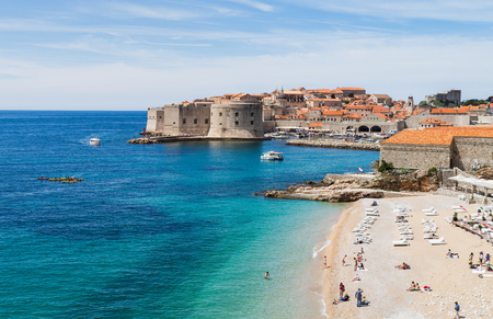 Tourists and locals enjoy the late springtime sunshine on the upmarket Banje Beach adjacent to the old town of Dubrovnik.