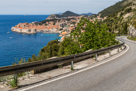 A winding single lane coastal road weaves along the side of steep limestone cliffs towards Dubrovnik.