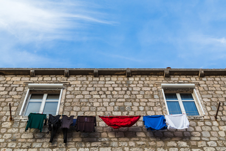 A typical scene whilst looking skyward in Dubrovnik as colourful laundry contrasts against the pale limestone facades. Stock Photo
