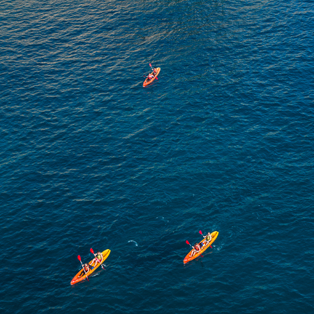 Tourists occupy three kayaks between Fort Lovrijenac & the city walls of Dubrovnik.