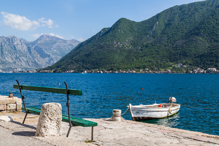 kotor: A bench seen facing out to the water in Perast seen at the foot of the rugged & rocky terrain of St Ilija on the Montenegro coastline.