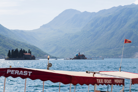 A tourist boat waits for passengers to board to visist the islets of St. George and Our Lady of the Rocks just off the coast in Perast. Stock Photo - 77864084