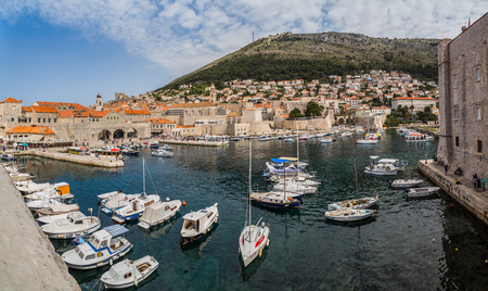 srd: A multiple image panorama of the small boats and yachts bobbing up and down in the old harbour of Dubrovnik on a Spring morning.  This was captured high up on the ancient city walls facing the old town and Srd Hill which overlooks Dubrovnik.