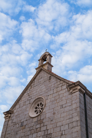 Looking skyward towards the bell on the top of a small church pictured just outside of the Dubrovnik city walls.