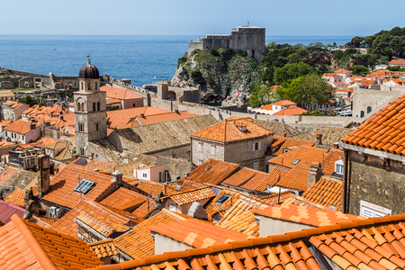 Looking over the orange terracotta rooftops of Dubrovniks old town from a high vantage point on the city walls.The Franciscan Monastery can be seen in the foreground whilst Fort Lovrijenac, a natural extension to the ancient walls sits in the background j