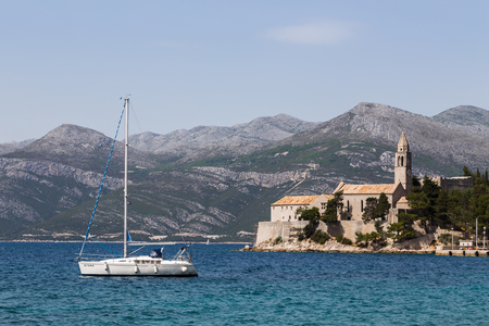 A yacht pictured off the coast of Lopud Island in the South of Croatia.  The Franciscan Monastery can be seen on the end of the promenade in the distance.