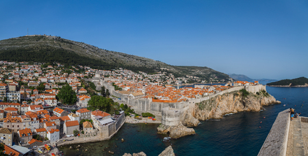 srd: A multiple image panorama captured from Fort Lovrijenac of tourists admiring the views across the old town of Dubrovnik, encased by its ancient city walls which slope up and down. Stock Photo