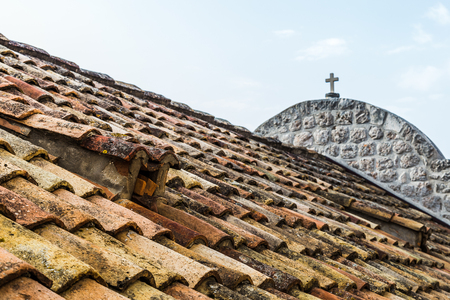 replaced: A typical terracotta tiled rooftop captured in the old town of Dubrovnik from the city walls at the start of the 2017 holiday season.  Many of the rooftiles were replaced during the 1990s Balkans war however this building still had the original ones.