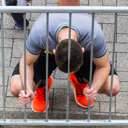 leaning by barrier: A young adult crouches down and catches his breath after finishing the 2017 Liverpool Rock n Roll marathon on 28 May 2017. Editorial