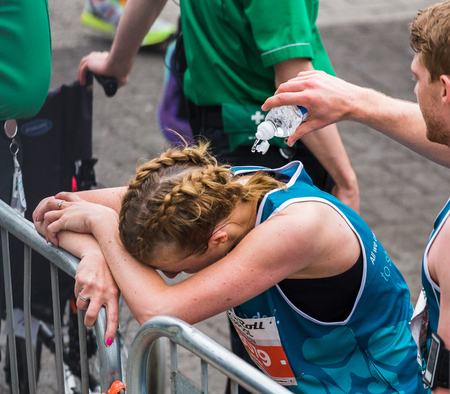 A man helps to cool off a young woman by splashing her with cold water at the end of the 2017 Liverpool Rock n Roll half marathon on 28 May 2017.