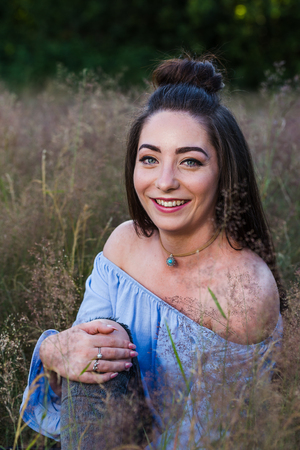 A gorgeous young woman sits in a meadow of long grass near Liverpool one summers evening pulling her knee gently towards her chest.