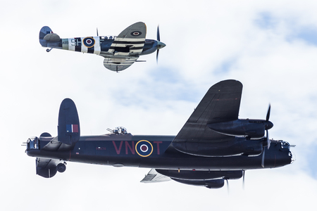A World War Two Lancaster is escorted by a Spitfire fighter (from the same era) above the sky of Blackpool at a free seaside airshow in August 2017.
