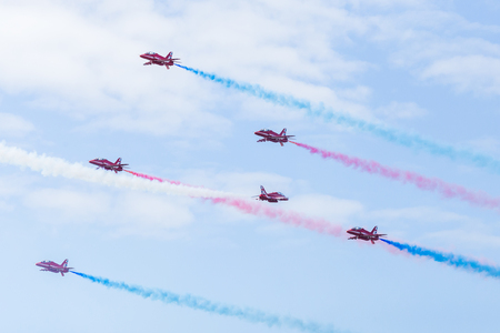 A single Red Arrow aircraft flies through a tunnel of five other aircraft flying towards it in the Goose manoeuvre at the Blackpool seaside airshow. Editorial