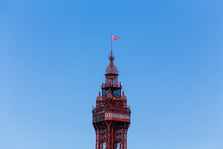 A Union Jack flaps in the wind high above the tall Blackpool tower.  This was captured during the annual Blackpool airshow.