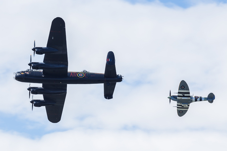 An old Spitfire escorts an RAF Lancaster above the skies of Blackpool at a free seaside airshow in August 2017.