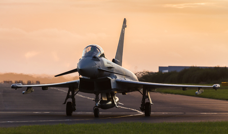 A Royal Air Force Typhoon jet taxis out towards the runway at Liverpool John Lennon airport at sunset ready for takeoff.