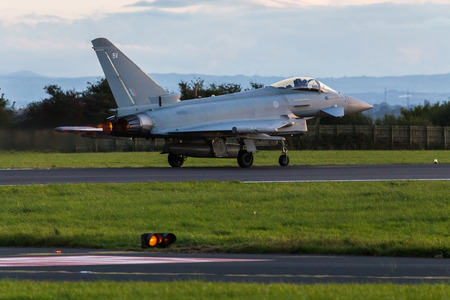 The afterburners on a Royal Air Force Typhoon FGR4 lights up the runway at Liverpool John Lennon airport during an autumn evening in 2017. Editorial