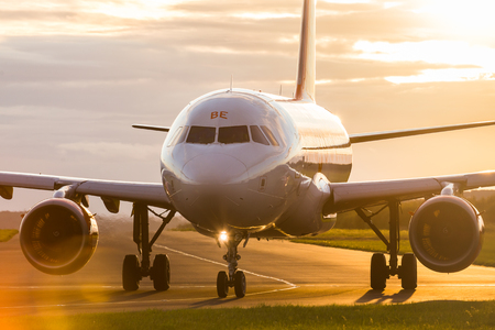 Backlit image taken at sunset of an Easyjet airliner taxiing out for takeoff at Liverpool John Lennon airport during the autumn of 2017.