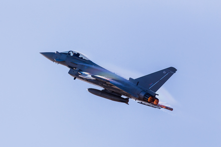 Zonlicht vangt de condensatie op de vleugels van de RAF Typhoon terwijl deze de Southport-vliegshow verlaat en een regenboog creëert.