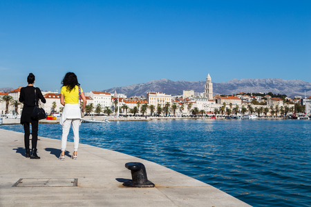 A couple of young women wonder along the quayside in Split towards the Riva - the famous waterfront lined by palm trees and cafes.