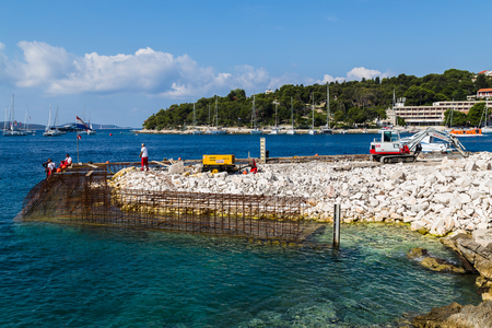 edge: Men work in the warm mediterranean sunshine of the autumn in Hvar Town to extend the promenade known locally as the Riva.