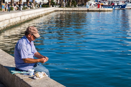 A fisherman prepares his hook to cast into the water at Matejuska the Fishermans port on the west end of Splits promenade called Riva. Editorial