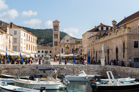 Main square of Hvar town anchored by the Renaissance-era Hvar Cathedral, pictured from the harbour end during a busy autumn day. Editorial