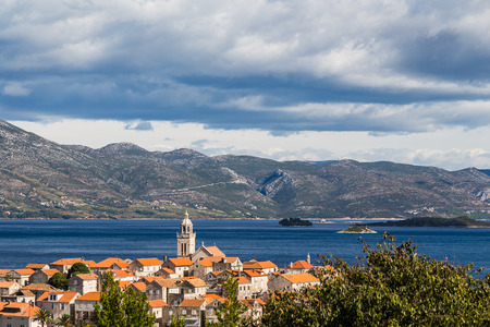 The buildings on the peak of Korcula old town seen against a backdrop of the blue waters of the Peljesac channel and then further back the Croatian mainland (the Peljesac peninsula).