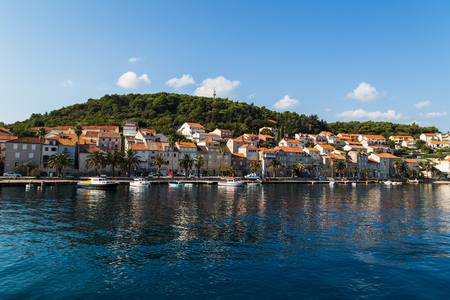 Pretty orange roof tops line the promenade west of Korculas old town - pictured under a blue sky one autumn morning. Stock Photo