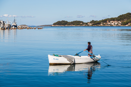 Ripples and reflections surround a man in his small white fishing boat as it approaches Vela Luka on Korcula Island.